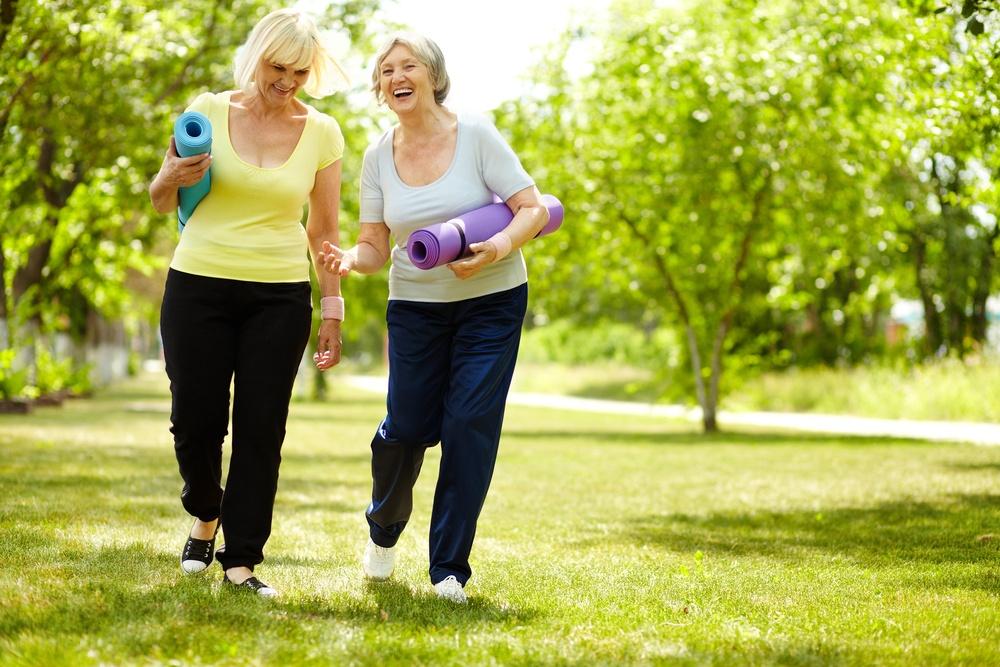 Happy women walking with yoga mats