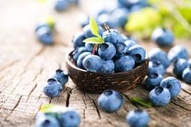 blueberries in basket on wood