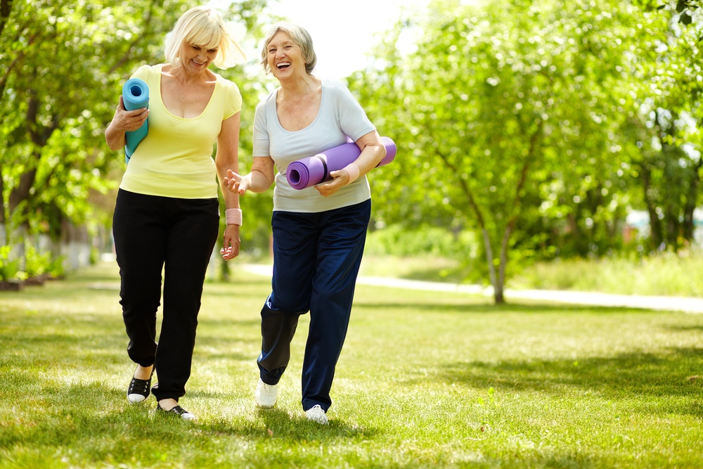 Happy women walking with yoga mats