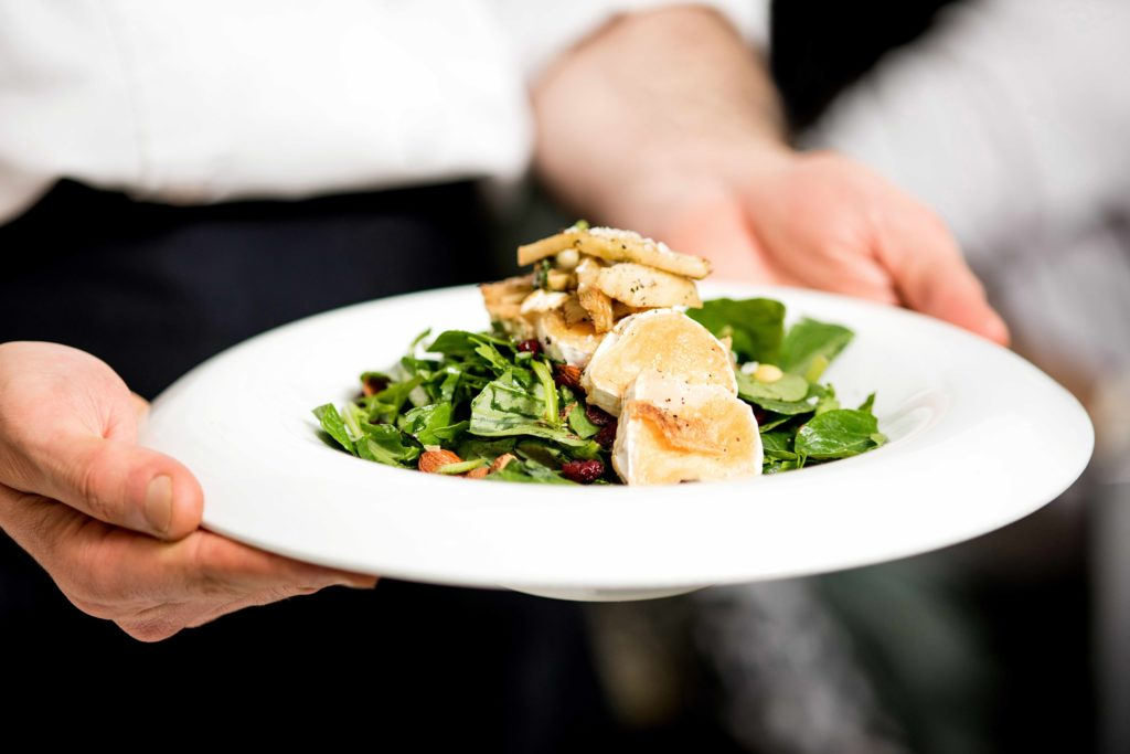 chef-holding-salad-on-plate-with-goat-cheese-1024x683