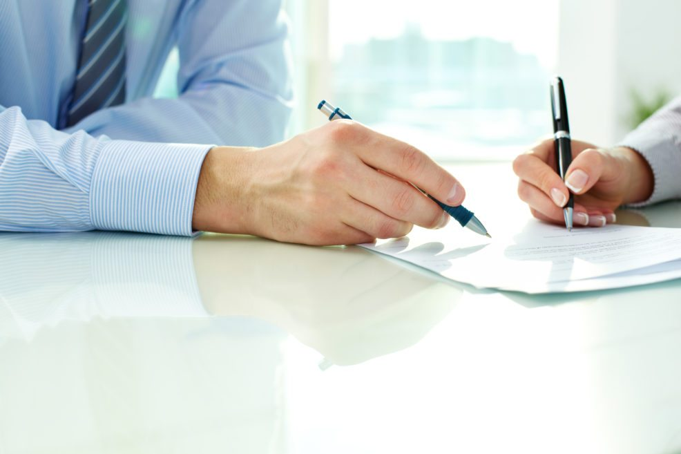 signing-a-document-986x657